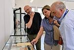 Foto von drei Personen in der Ausstellung der Gedenkstätte vor einer Vitrine mit Effekten von ehemaligen Häftlingen