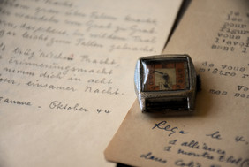 Photo of a wristwatch next to old papers