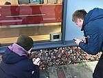 Zwei Personen vor einem kleinen Bildschirm mit Bildinformationen in der Gedenkstätte