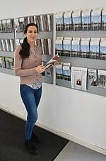 Antanina Chumakova vor Flyerwand der KZ-Gedenkstätte Neuengamme
