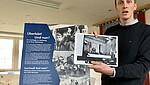 Foto von Lennart Onken im Depot der KZ-Gedenkstätte Neuengamme vor einer Ausstellungstafel